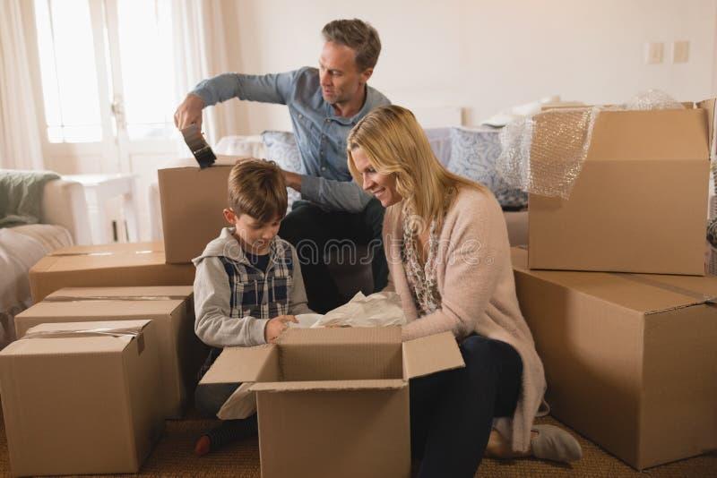 Familj som packar upp kartonger i deras nya hem royaltyfria foton