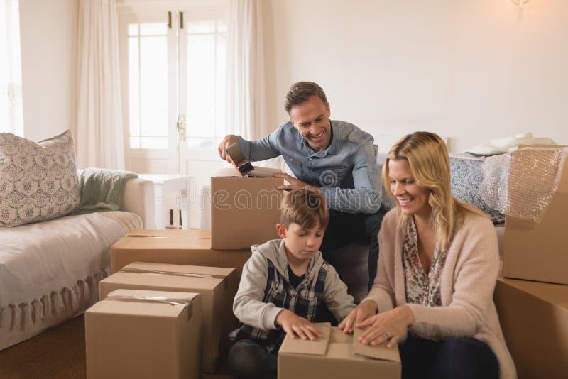 Familj som packar upp kartonger i deras nya hem arkivfoton
