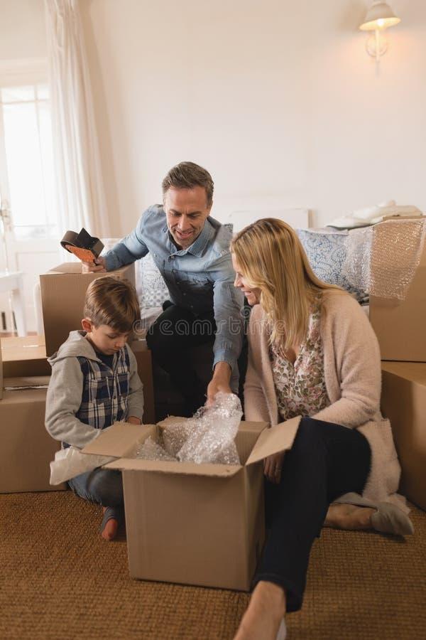 Familj som packar upp kartonger i deras nya hem fotografering för bildbyråer