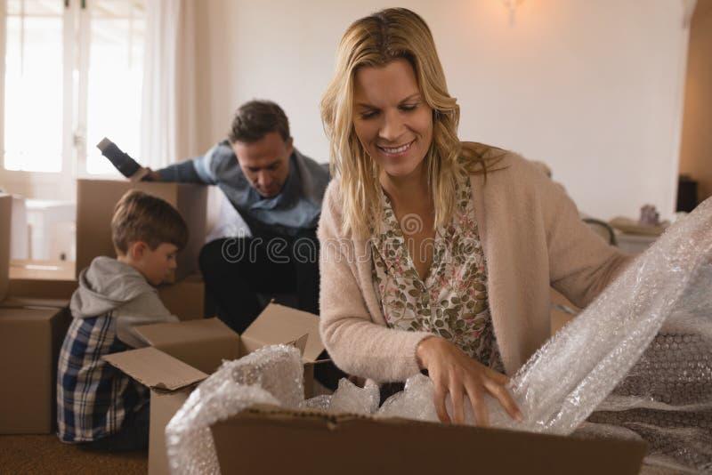 Familj som packar upp kartonger i deras nya hem royaltyfria bilder