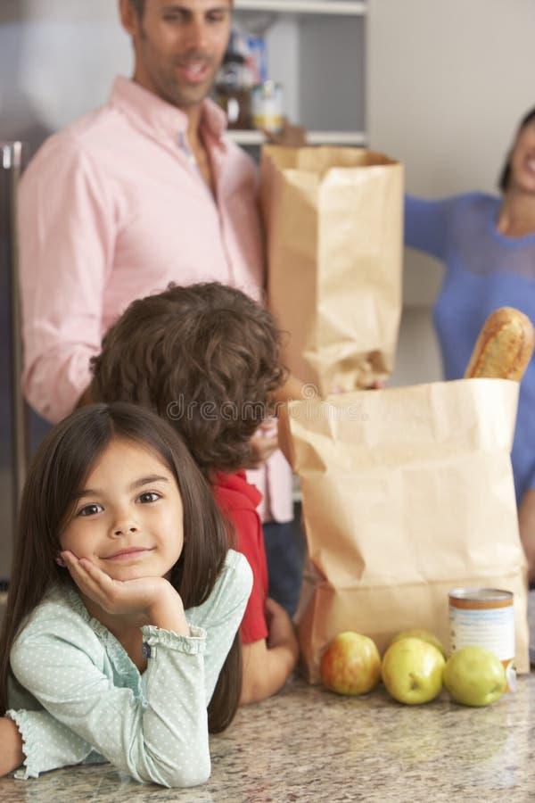 Familj som packar upp livsmedelsbutikshopping i kök arkivfoton