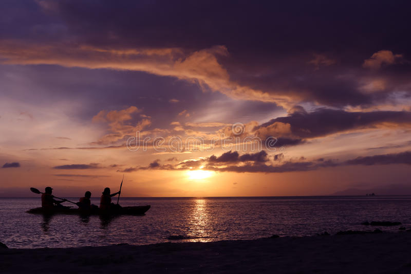Familj som paddlar en kajak vid havet royaltyfri foto