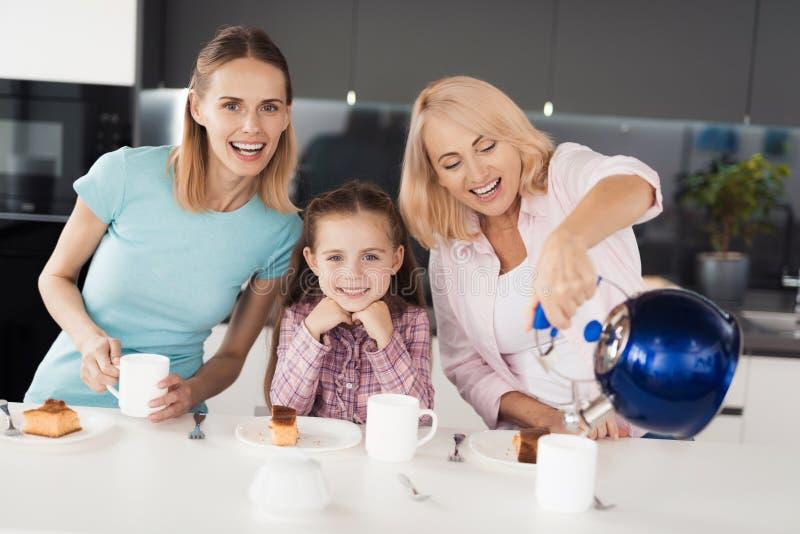 Familj som poserar i köket i processen av att dricka för te En äldre kvinna häller te från en tekanna in i en kopp arkivbild