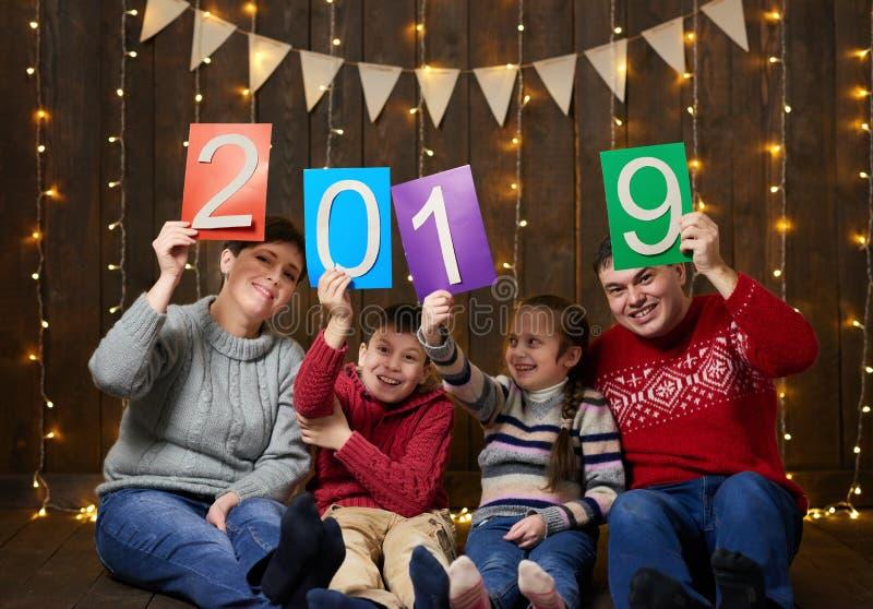 Familj som poserar med text för nytt år 2019, sitter på mörk träbakgrund med julljus och flaggor och har gyckel VinterH arkivbild