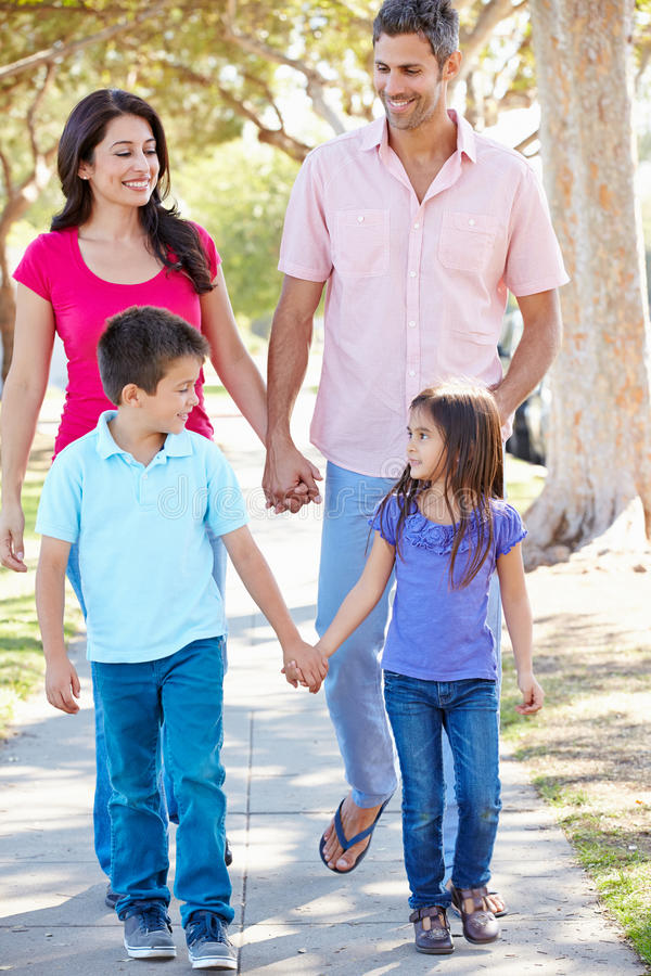 Familj som promenerar den förorts- gatan royaltyfri bild