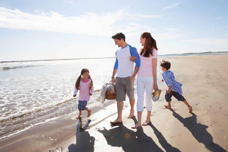 Familj som promenerar stranden med picknickkorgen royaltyfri foto