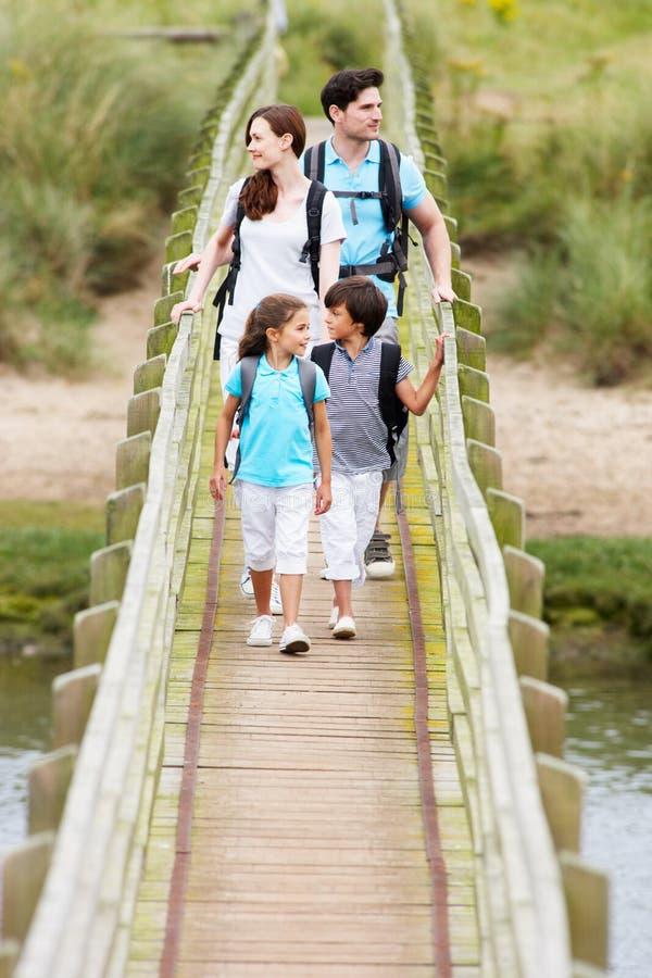 Familj som promenerar träbron royaltyfria bilder