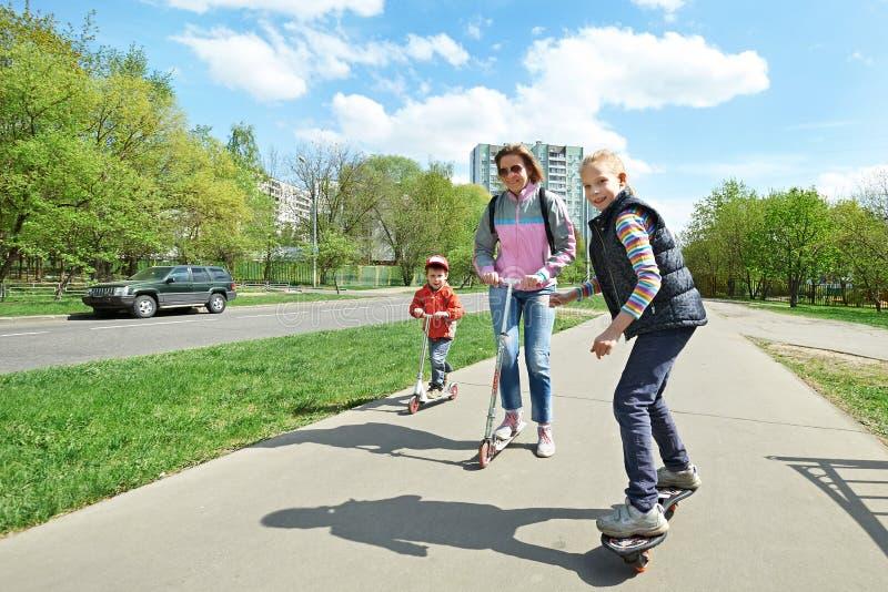 Familj som rider en skateboard och en sparkcykel arkivfoton