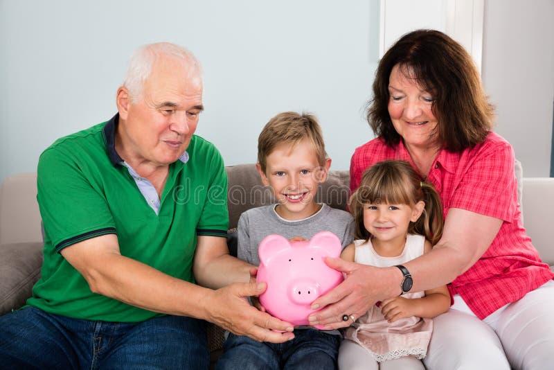 Familj som rymmer Piggybank hemmastadd fotografering för bildbyråer