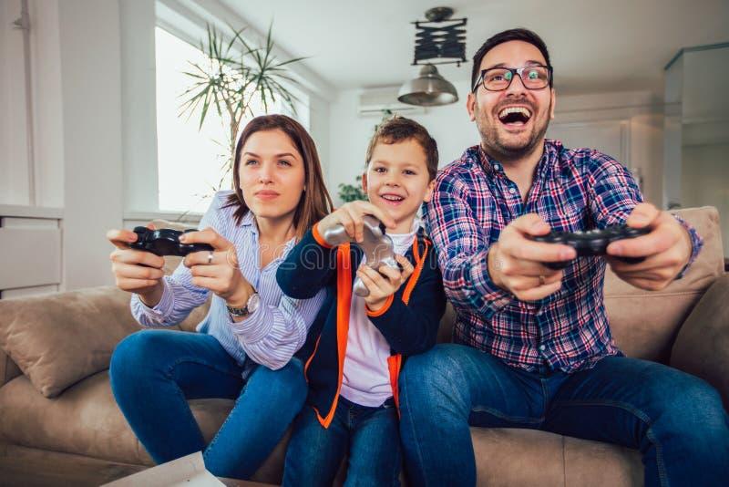 Familj som sitter p? en soffa och spelar videospel och ?ter pizza royaltyfri foto