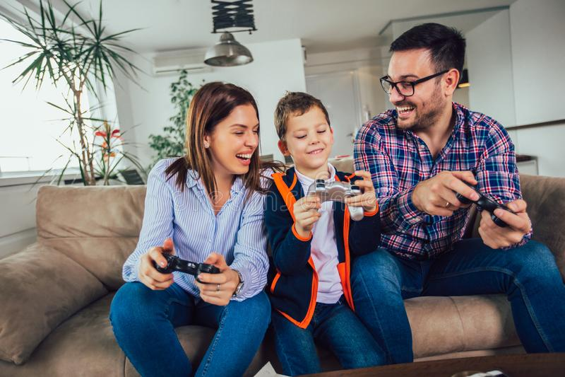 Familj som sitter p? en soffa och spelar videospel och ?ter pizza arkivbild