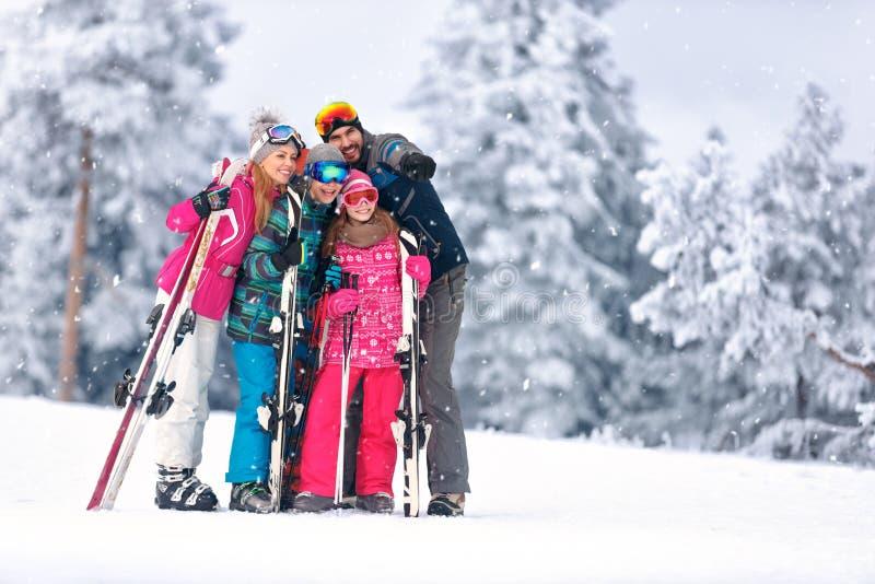 Familj som skidar tillsammans på berget arkivbild