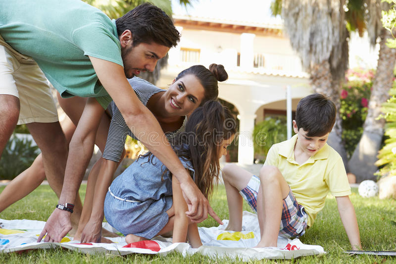 Familj som spelar balansera leken i trädgård royaltyfri bild