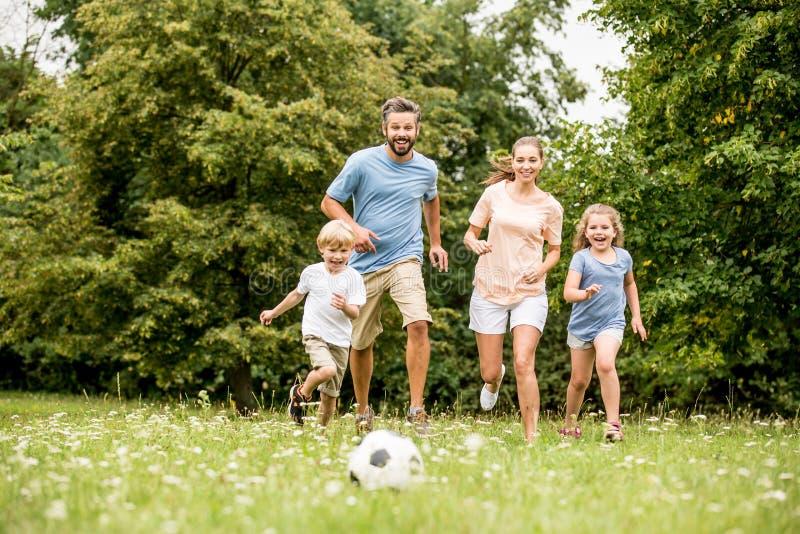 Familj som spelar fotboll i sommar royaltyfri foto