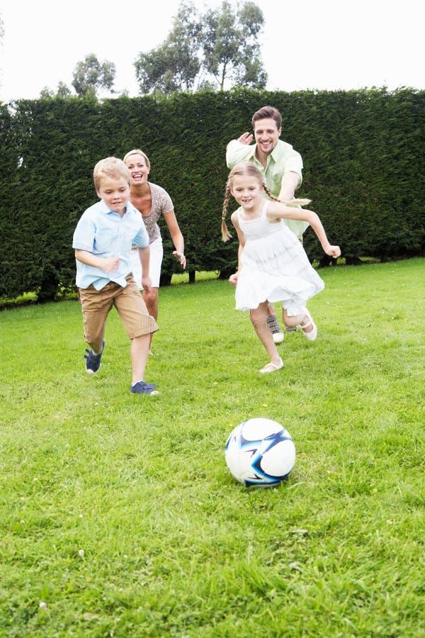 Familj som spelar fotboll i trädgård arkivbilder