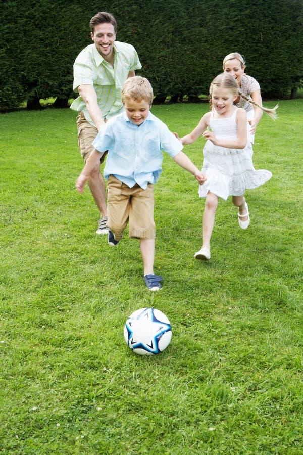 Familj som spelar fotboll i trädgård royaltyfri bild