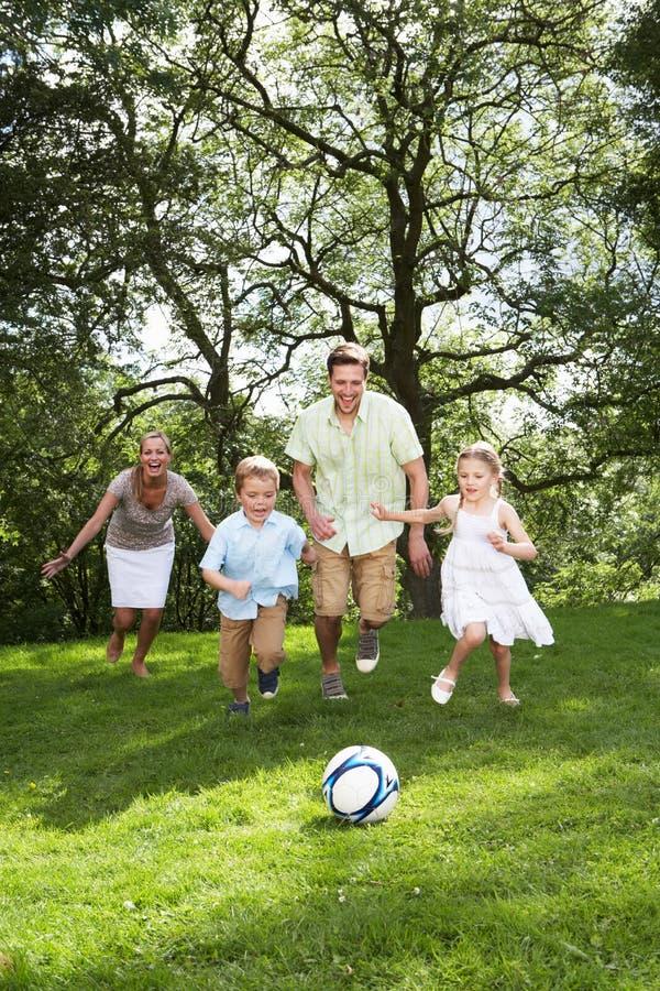 Familj som spelar fotboll i trädgård arkivbild