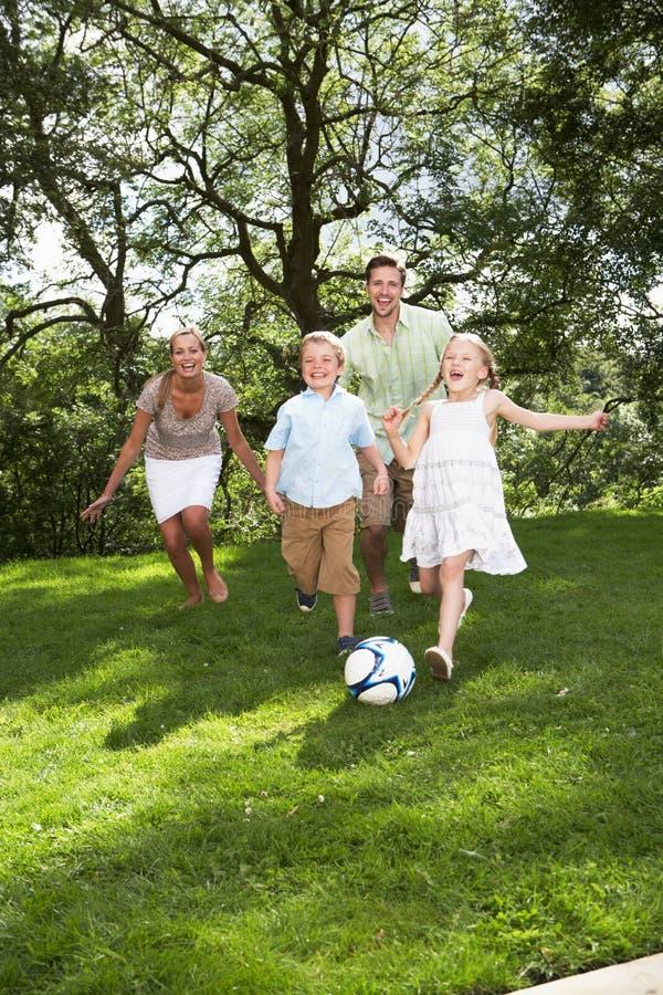 Familj som spelar fotboll i trädgård arkivfoton