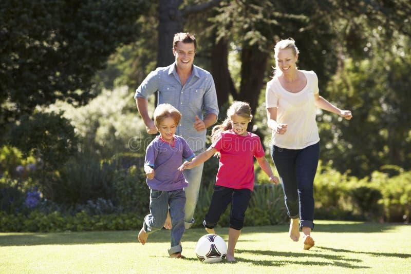 Familj som spelar fotboll i trädgård tillsammans arkivfoto