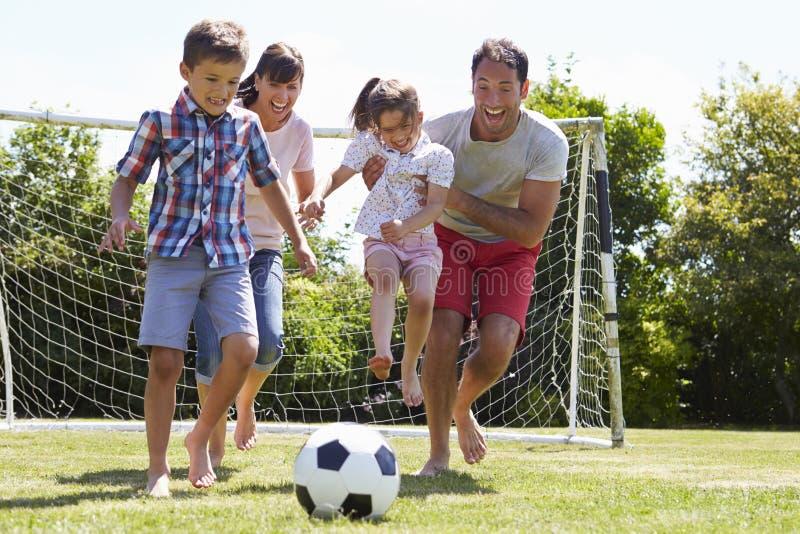 Familj som spelar fotboll i trädgård tillsammans royaltyfri bild