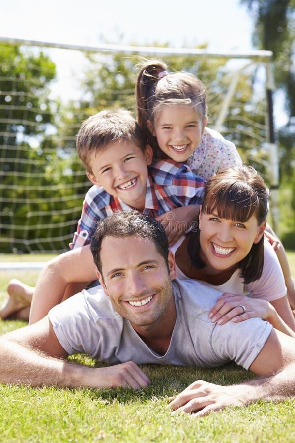 Familj som spelar fotboll i trädgård tillsammans royaltyfri fotografi