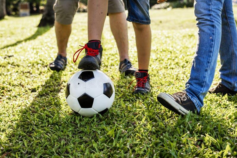 Familj som spelar fotboll i trädgården arkivfoto