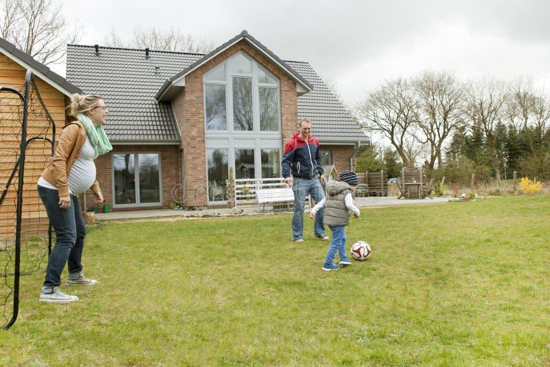 Familj som spelar fotboll i trädgården royaltyfria foton