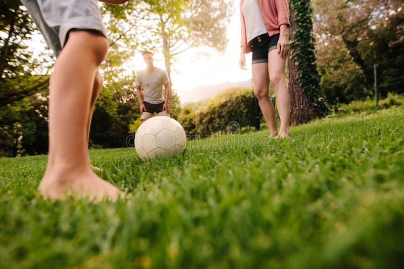 Familj som spelar fotboll i trädgårds- gräsmatta arkivbild