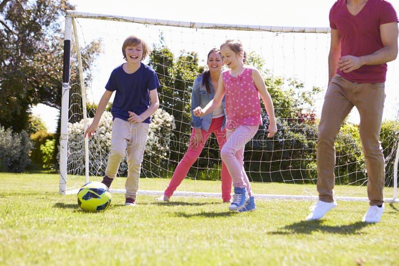 Familj som spelar fotboll tillsammans royaltyfri fotografi