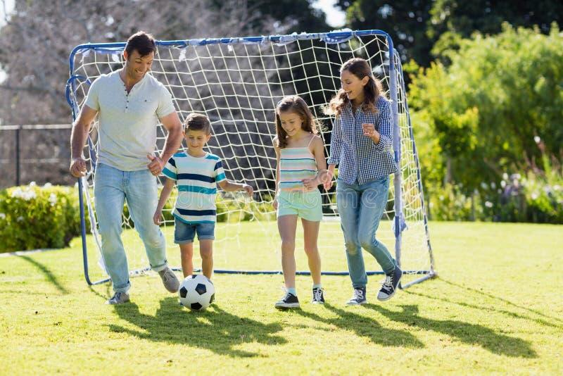 Familj som spelar fotboll tillsammans på parkera royaltyfria foton