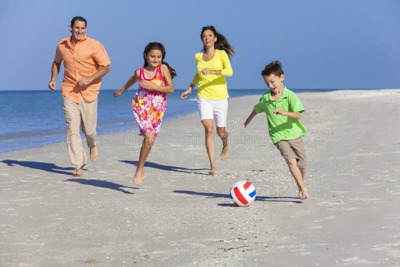 Familj som spelar fotbollfotboll på stranden arkivfoto