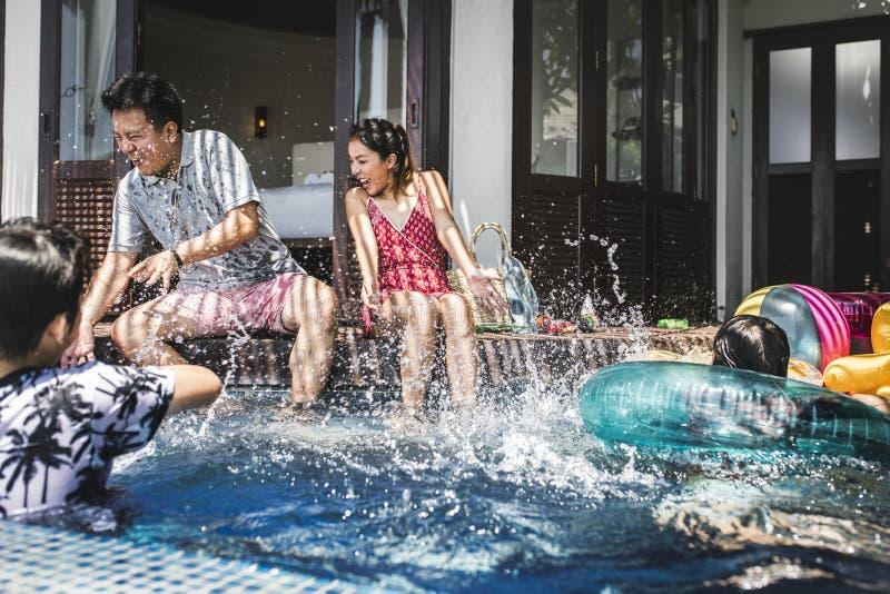 Familj som spelar i en pöl royaltyfri fotografi