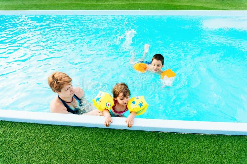 Familj som spelar i simbassäng royaltyfria bilder