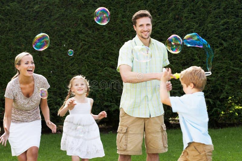 Familj som spelar med bubblor i trädgård royaltyfri bild