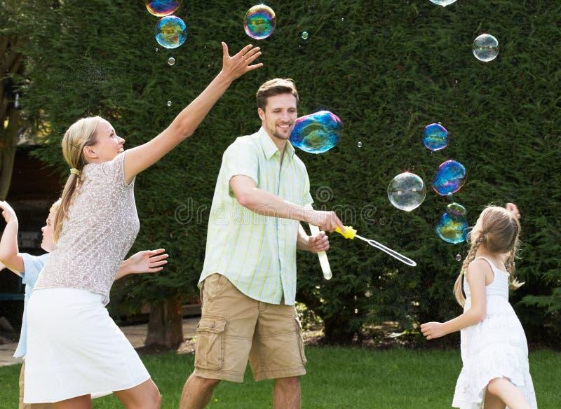 Familj som spelar med bubblor i trädgård arkivfoto
