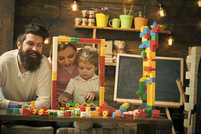 Familj som spelar med den hemmastadda konstruktörn Fadern, modern och sonen spelar nära stor ramkonstruktion som göras ut ur leks royaltyfria bilder