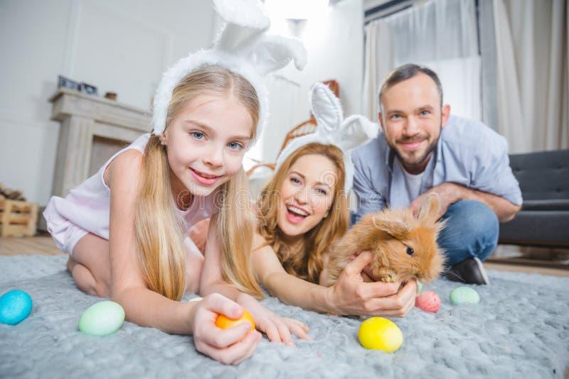 Familj som spelar med kanin royaltyfria foton