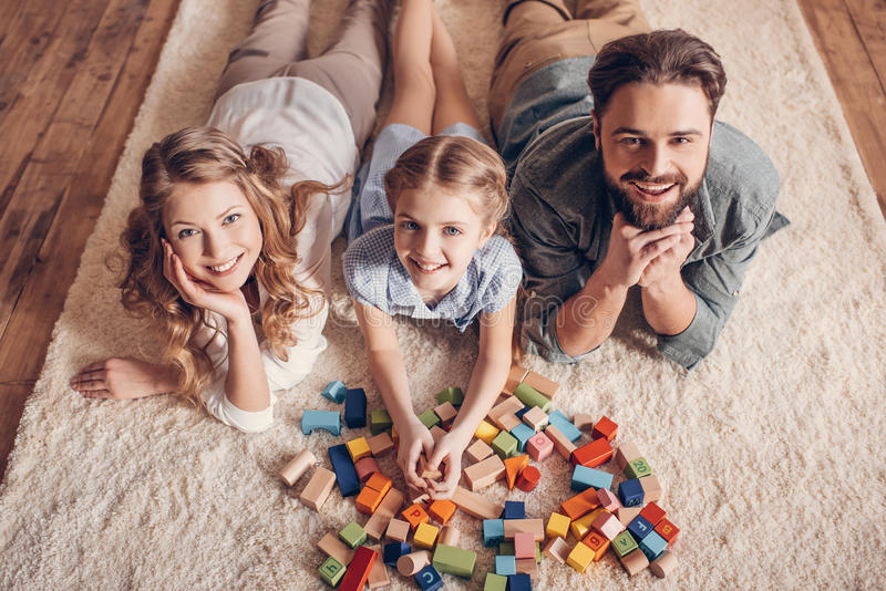 Familj som spelar med konstruktörn och hemma ligger på golv arkivfoton