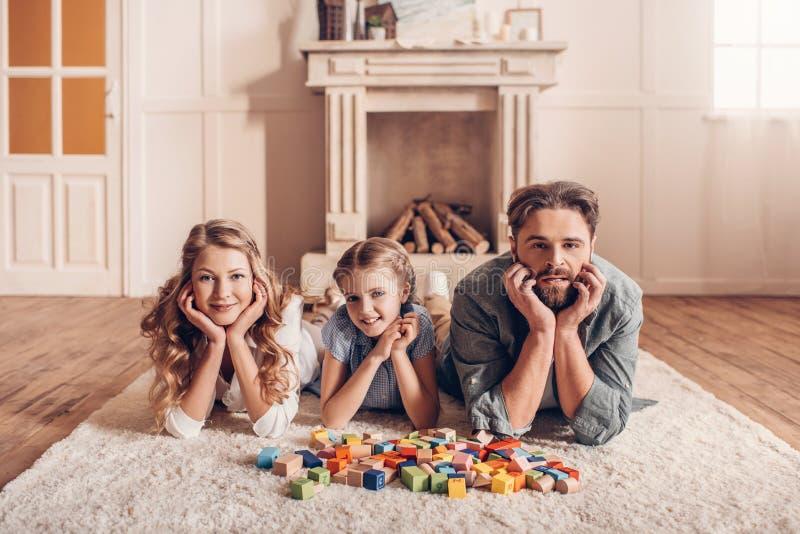 Familj som spelar med konstruktörn och hemma ligger på golv royaltyfria foton