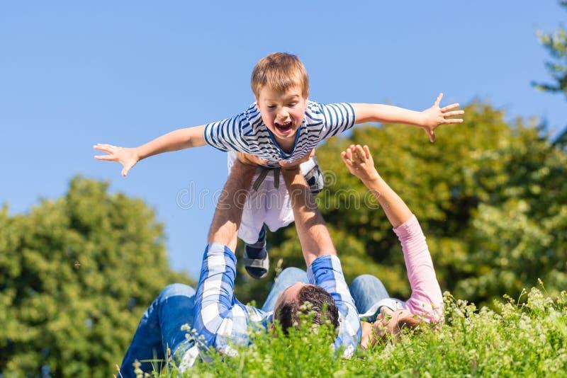 Familj som spelar med sonen som ligger i gräs på äng royaltyfri bild