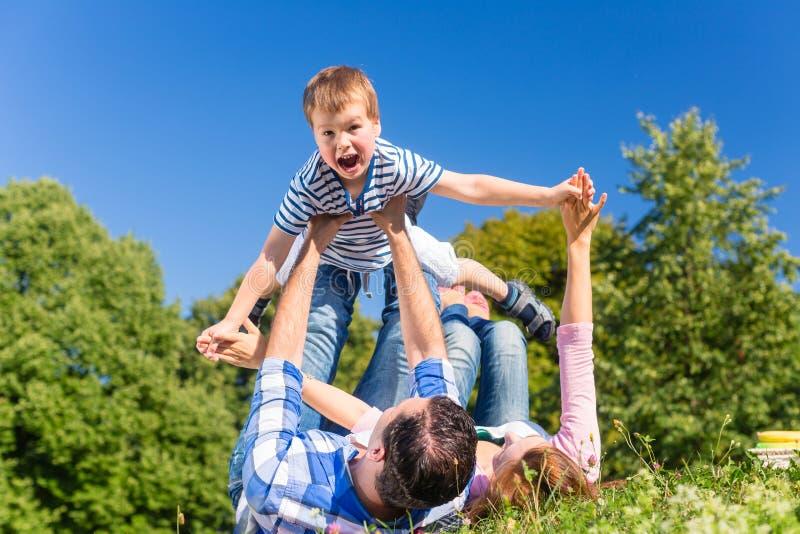 Familj som spelar med sonen som ligger i gräs på äng arkivfoton