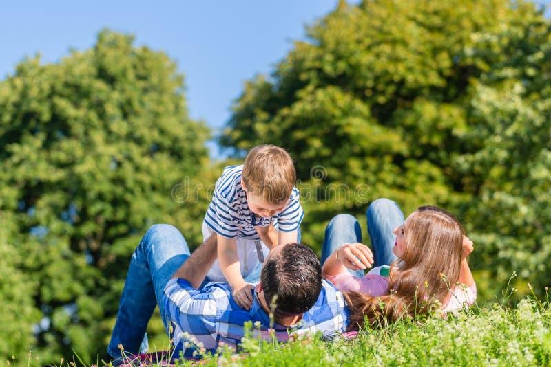 Familj som spelar med sonen som ligger i gräs på äng royaltyfri fotografi