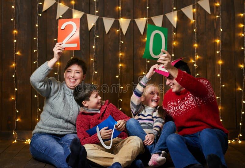 Familj som spelar med text för nytt år, sitter på mörk träbakgrund med julljus och flaggor och har gyckel vinterholid arkivfoton