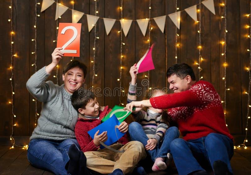 Familj som spelar med text för nytt år, sitter på mörk träbakgrund med julljus och flaggor och har gyckel vinterholid arkivfoto