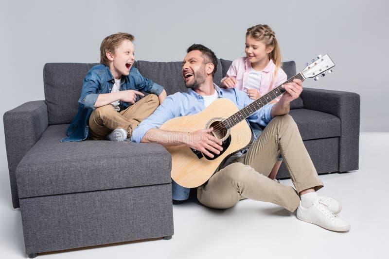 Familj som spelar på gitarren och sjunger och att spendera tid tillsammans, medan sitta på soffan royaltyfri foto