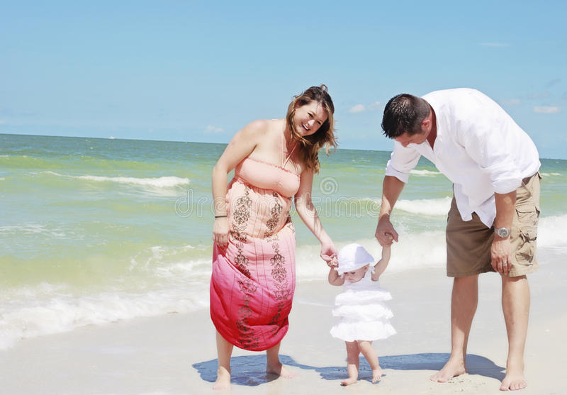 Familj som spelar på stranden arkivfoto