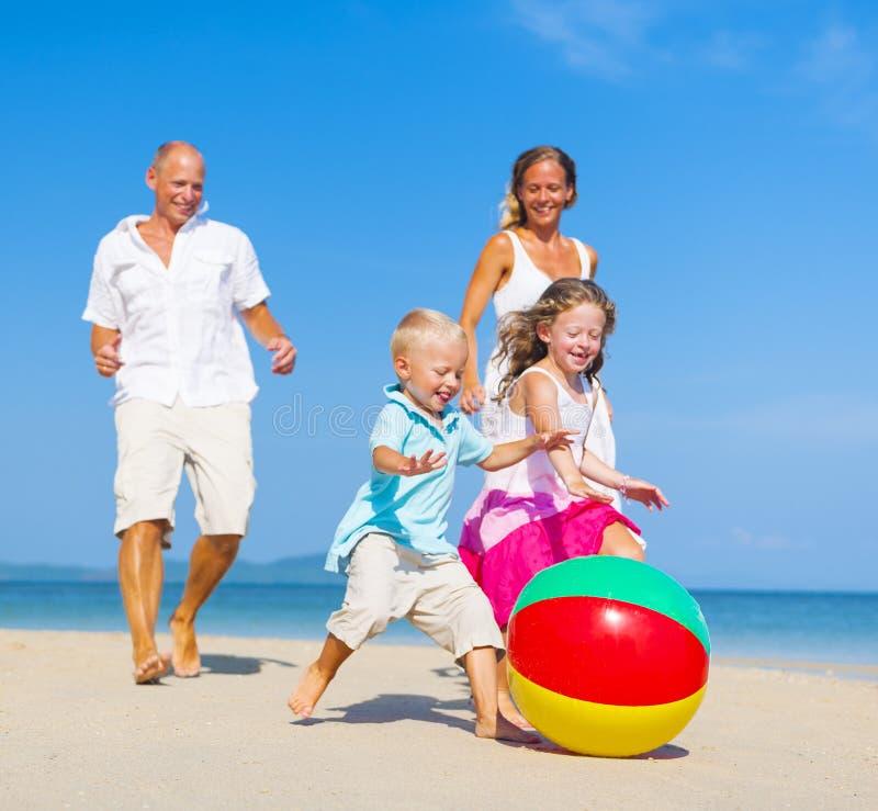 Familj som spelar på stranden arkivbilder