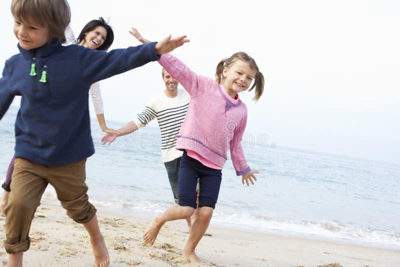 Familj som spelar på stranden tillsammans arkivfoto