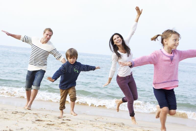 Familj som spelar på stranden tillsammans arkivfoton
