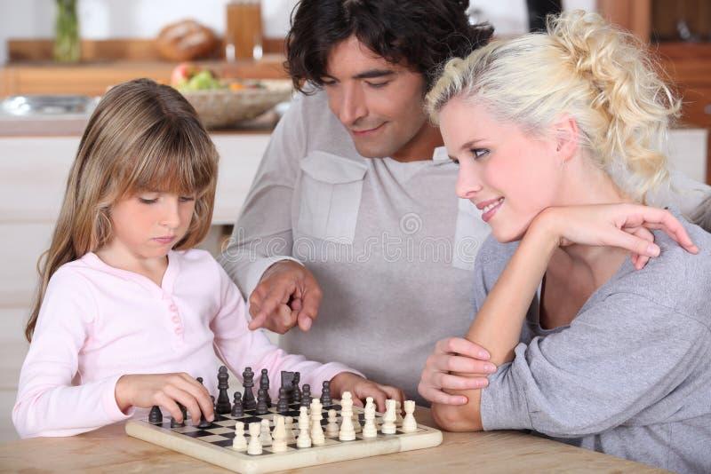 Familj som spelar schack arkivfoton